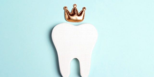 Tooth in the crown on a blue background. Happy Dentist's Day concept.